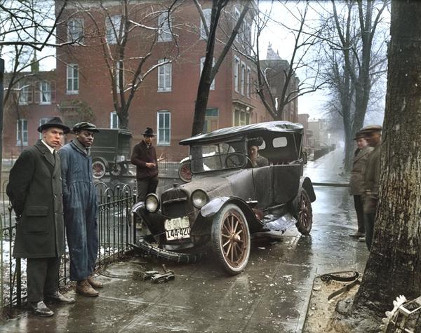Vemos en la foto varias personas que ven un carro accidentado y una mujer al volante se observ au ndia invernal y arboles sin hojas