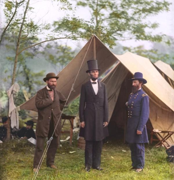 Tenemos la imagen de tres hombres dos con trajes y sombreros cubilos y uno con uniforme militar tambien vemos naturaleza y unas carpas
