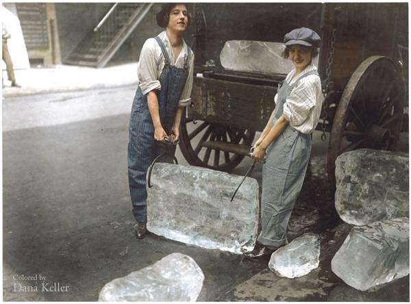 Tenemos dos mujeres  subiendo unos grandes cubos de hielo a un camión antiguo quedan en el piso varios cubos mas