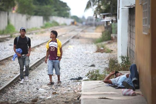 Ahora vemos a dos hombres muy jóvenes  que caminan al lado de la carrilera del tren y otro que descansa acostado en el piso