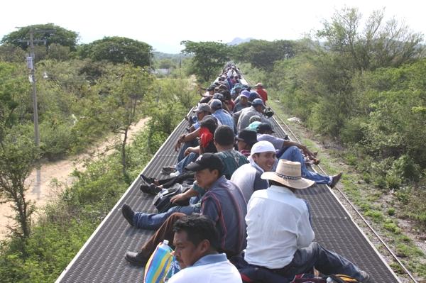 Tenemos a muchos hombres que  viajan en un planchon de tren  a su sitio de destino