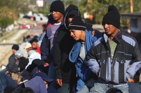 varios hombres muy jóvenes esperan  algo para continuar la marcha