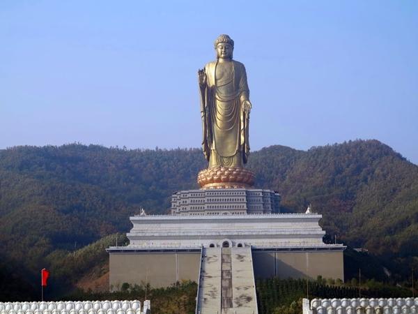 Una estatua dorada de Buda sobre un pedestal y al fondo montañas
