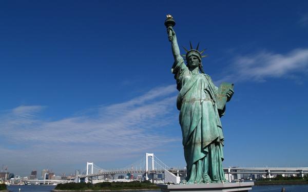 Estatua en color blanco sobre un gran pedestal lleva una antorcha iluminada en su mano derecha se destaca una corona de puntas sobre su cabeza al fondo una gran ciudad