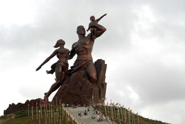 Imagen grande  en tono bronce se observa una familia mirando al infinito desde un pedestal alto