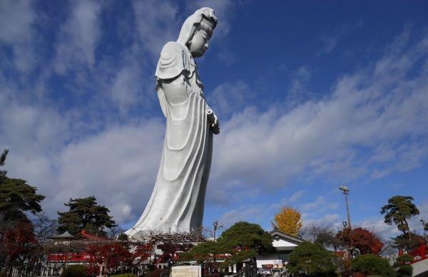 Estatua en color blanco femenina sobre un gran pedestal con rostro inclinado en posición de meditacion