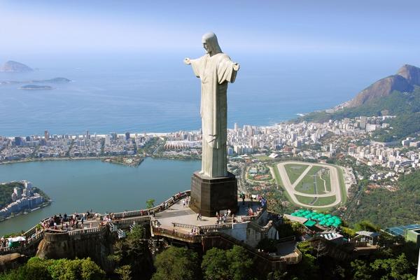 estatua en gris sobre un monte con los brazos abiertos dominando abajo una gran ciudad