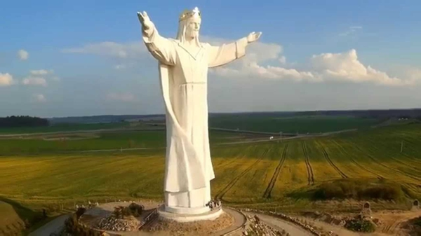Imagen colosal en color blanco con manos extendidas sobre pedestal dominando un inmenso valle
