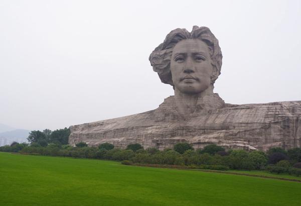 Figura de una gran cabeza gris sobre inmenso pedestal dominando un gran valle