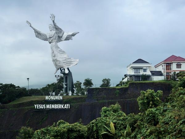 Estatua en acero con brazos  arriba pedestal en cemento observándose al fondo una pequeña ciudad