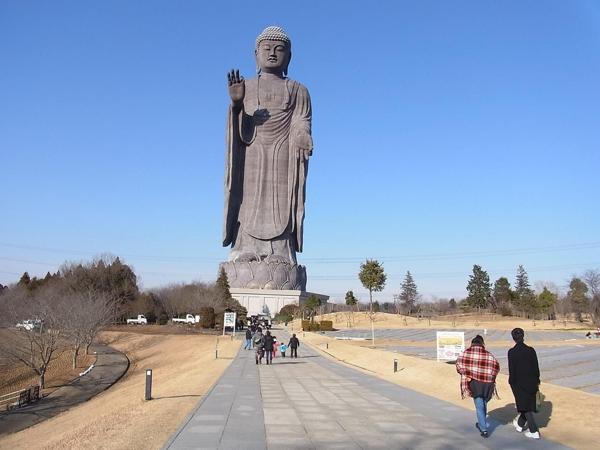 Imagen de Buda color gris sobre un pedestal bajo con una mano en posición de saludo