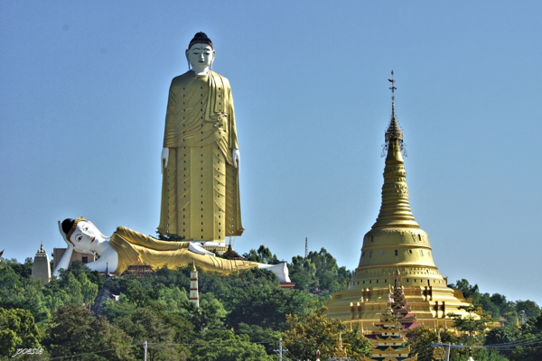 Figura gigante dorada observando a otra imagen dorada en posición de descanso al lado de una pagoda