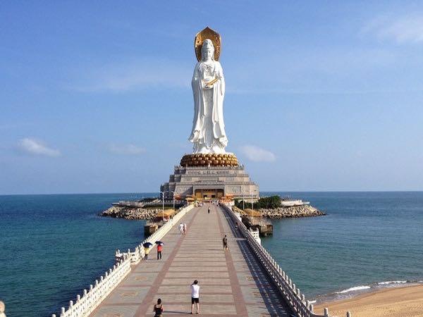 Imagen femenina toda en blanco de una divinidad en un pedestal a la orilla del mar