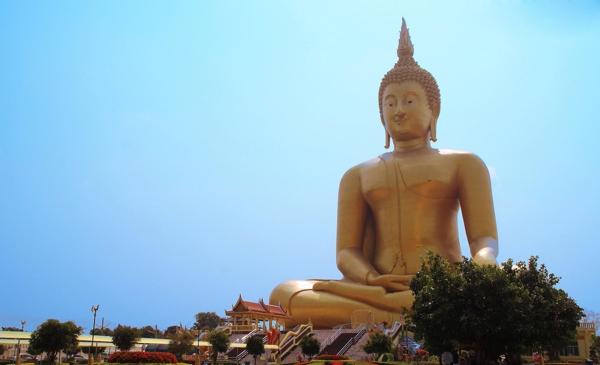 Estatua gigante en tono dorado sentada sobre pedestal en una colina
