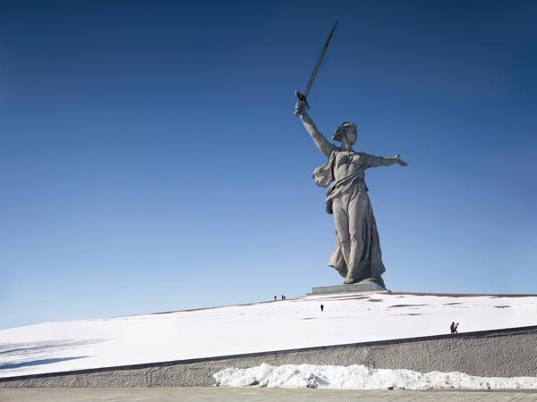 Imagen femenina color blanco sobre una colina blandiendo una espada en su mano derecha