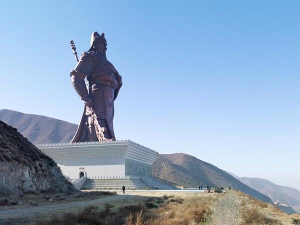 monumental estatua color gris sobre una colina en un gran pedestaly se divisa al fondo un gran valle.