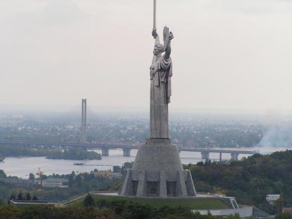 Figura femenina en color gris sobre un pedestal llevando una espada en su mano derecha se observa al fondo una gran ciudad
