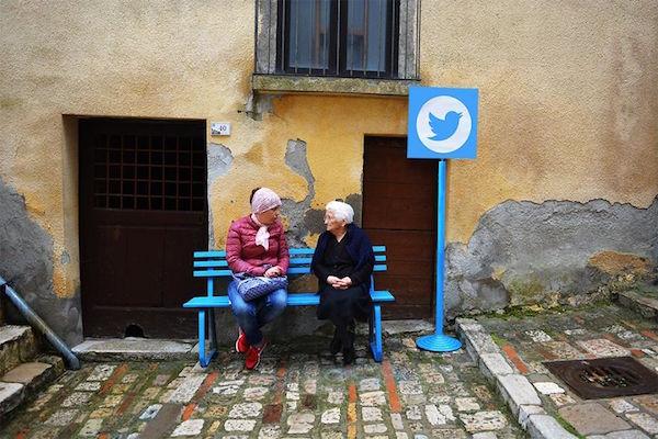 Dos personas sentadas en una banca azul y al lado un poste con el logo de twitter