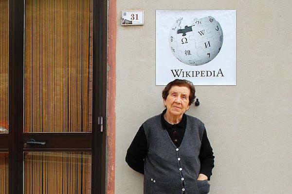 Una señora de edad recostada en la pared y sobre la cabeza de ella esta el logo de wikipedia