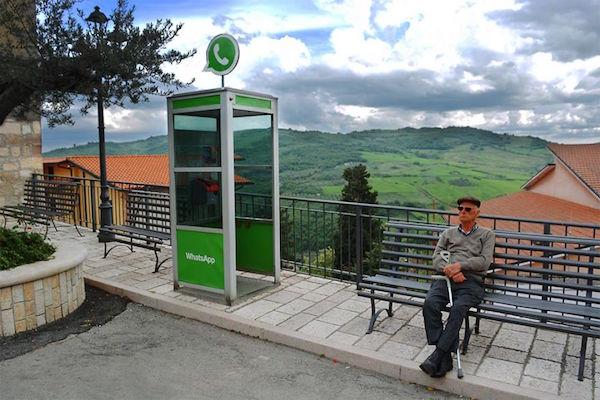 Un telefono publico todo de verde y en la parte de encima tiene el logo de whatsapp