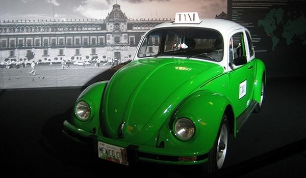 Tenemos un carro  verde pequeño el famoso escarabajo como taxi se ve una Plaza y gente que pasa por ahí  detrás del carro hay un planisferio