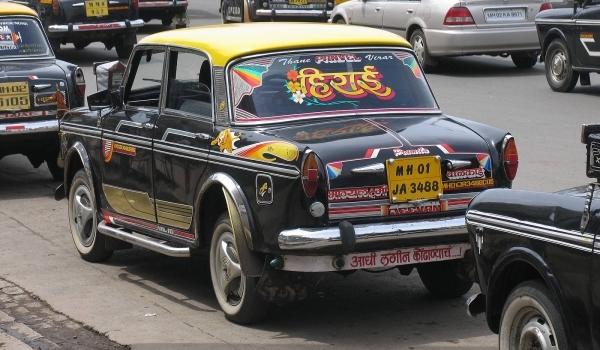 Vemos un carro negro con pinturas amarillas que esta dentro de una cantidad de carros que se desplazan por una calle llena de trafico