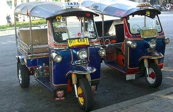 Miramos aquí un par de carros iguales en color azul  muy pequeños  tambien vemos otros carros  y motos al frente