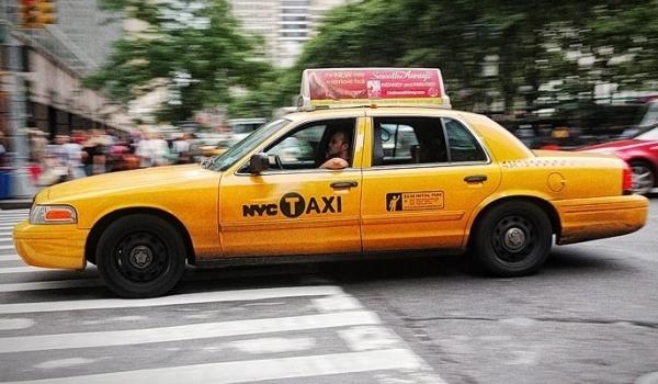 Tenemos un taxi amarillo que  lleva en su parte alta una publicidad de algo pasa por  un sitio con zona verde y edificios