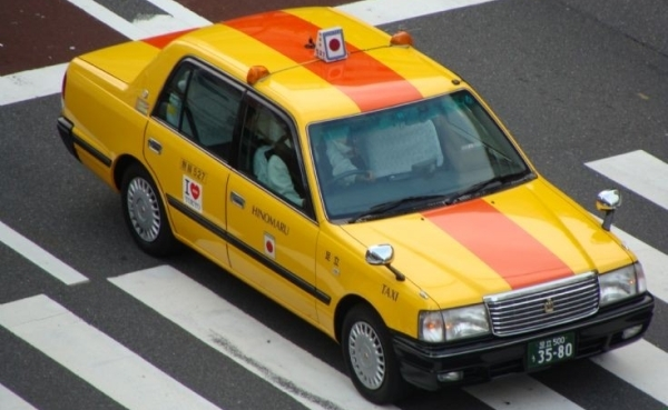 Vemos un taxi amarillo con franjas naranjas  que se desplaza por una ciudad