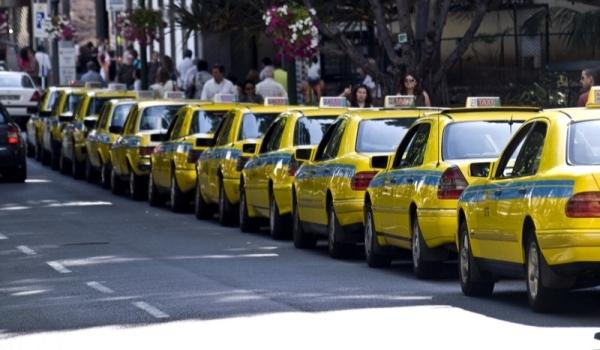 Tenemos una flotilla de carros amarillos bien alineados mientras muchas personas circulan cerca de ellos