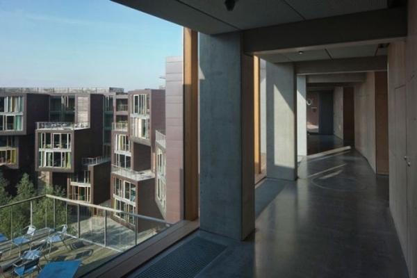 Vemos un pasillo y desde allí se ve la terraza con su mesa y sillas grandes vitrales  tambien observamos el mismo edificio de antes