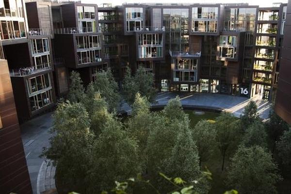 Vemos el conjunto del esdificio redondeado con sus vidrieras y sus zonas verdes y altos arboles