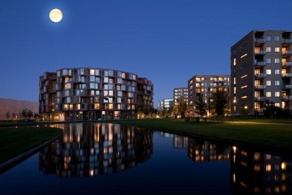 Vemos el mismo conjunto de edificios redondeados  con sus zonas verdes y      un estanque  y en la noche  una luna hermosa los alumbra