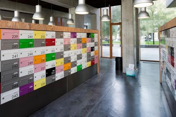 Vemos un sitio grande donde sobre una pared se ven una cantidad de cajitas en diferentes colores y con un numero y mas arriba penden muchas lamparas para iluminar  la sala