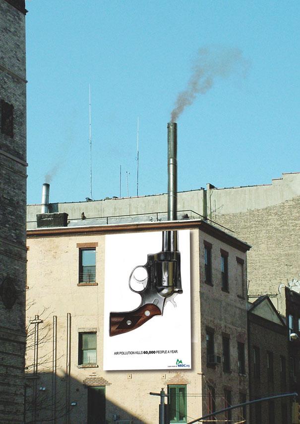 Observamos una pared blanca donde esta pintado un revolver donde su cañon sobresale en  el techo haciendo las veces de chimenea por donde sale un poco de humo esta publicidad muestra el daño que hace la polucion cada año en el planeta