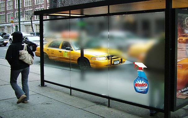 Vemos un taxi a traves de una vidrio que escibe publicidad en ese momento esta opaco el vidrio y el taxi se ve poco vemos grabado el nombre de un producto limpia vidriod