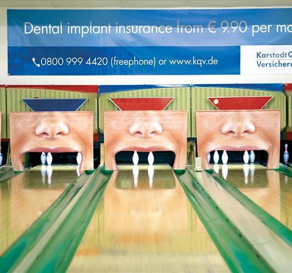 Vemos unas canchas de Bolos donde los boliches simulan dientes perdidos para publictar implantes dentales