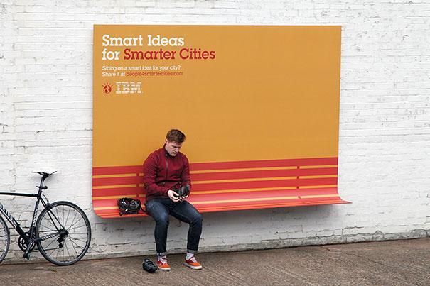 Un hombre sentado en una saliente que tiene un aviso gigante donde habla de la gente inteligente en ciudades inteligentes a su lado tiene una bici