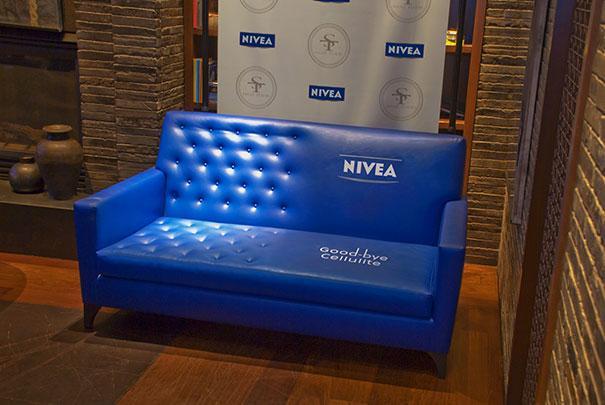 Observamos una pared rustica y al lado un sofa en tela azul donde la mitad tiene un tipo de abulnados con undidos por botones y la otra mitad del sofa esta ccompletamente liso y anuncia crema nives contra la celulitis