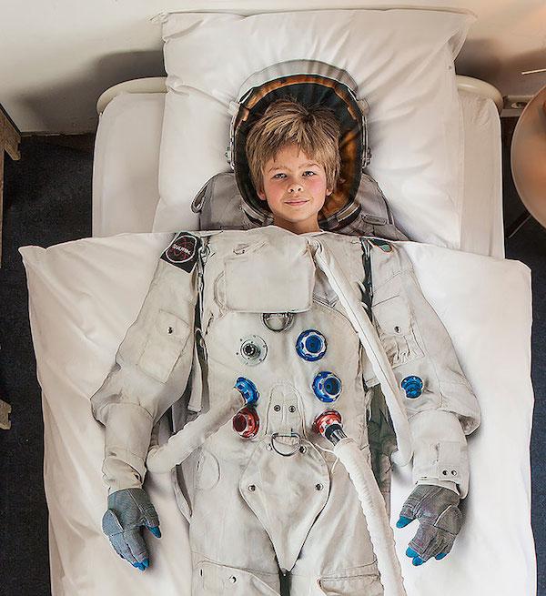 Observamos un edredón blanco con una figura de un astronauta y debajo un niño rubio que parece que tuviera puesto el traje de astronauta