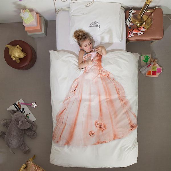 Un cama donde hay un edredon blanco que trae dibujado un hermoso traje largo para niña y donde la niña se cubre con el y parece que ella tuviera puesto el vestido