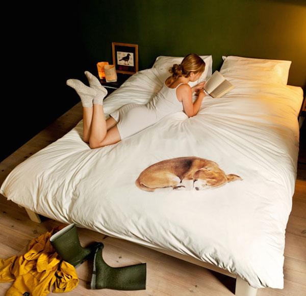 Observamos una cama amplia con sabanas blancas y mujer joven vestida de blanco que lee un libro a su lado una figura de perro que dormita a su lado
