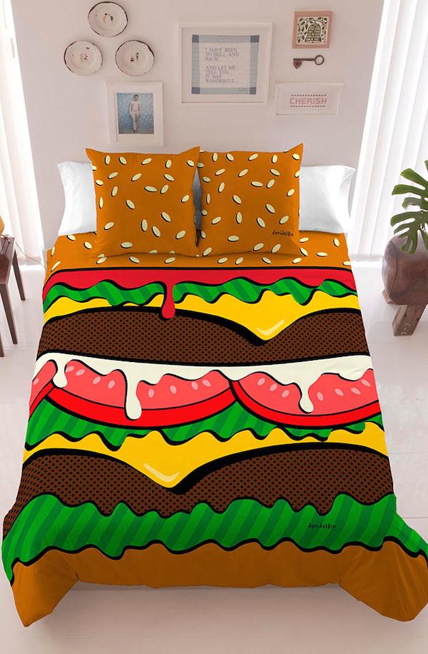 Vemos un hermoso tendido con colores muy fuertes y almohadas con semillas esparcidas  es la figura de una gran hamburguesa en  la pared hay platos de adorno
