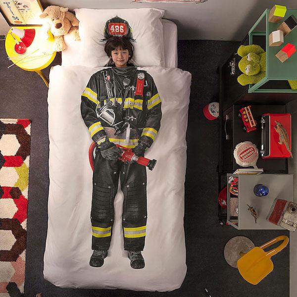 Vemos un edredón  que tiene pintado un traje de bombero y dentro un niño que parece lo llevase puesto  al lado de la cama hay una mesa donde se observa obetos propios del mundo bomberil