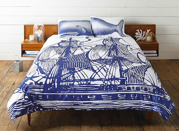Observamos una cama amplia con un tendido donde hay dos grandes veleros en color azul y las dos almohadas al juntarles forman un simpático cachalote
