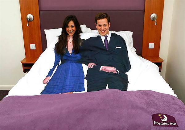 Una cama muy amplia se ve una pareja acostada con lindos trajes pero ellos están cubiertos con un edredón que  tiene estos trajes pintados y da otra idea