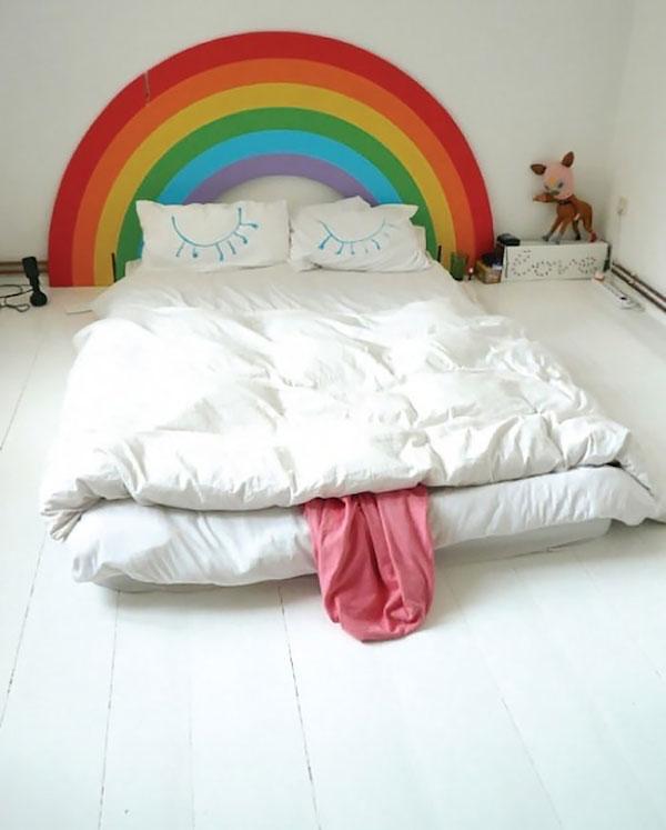 Vemos una cama grande donde el testero de la cama muestra un arco iris en colores fuertes y luego las dos almohadas muestran las pestañas  de un muñeco