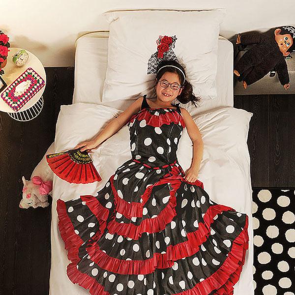 Vemos en una cama con tendidos blancos a una niña con un traje de española  con puntos blancos y rojos con abanico y un  adorno para la cabeza  al lado tiene un muñeco de peluche pero vemos que el traje ella no lo lleva ella es  el tendido el que lo lleva