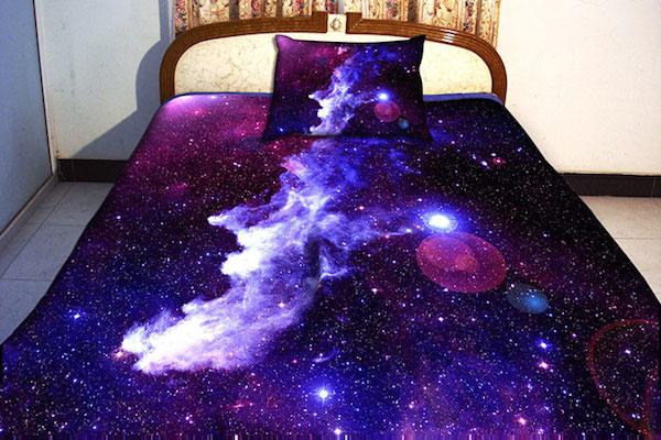 Vemos una cama con  un tendido que representa el universo plagado de estrellas y galaxias en colores morados y lilas y brillantes estrellas