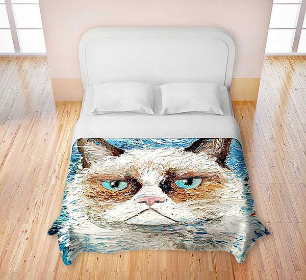 Observamos una cama tendida con sabanas y almohadas en blanco pero en la parte de abajo hay un  pequeño tendio con la figura en azul de un bello gato